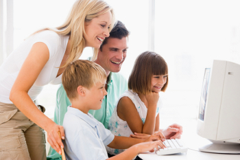 A family gathers at the computer to watch their video